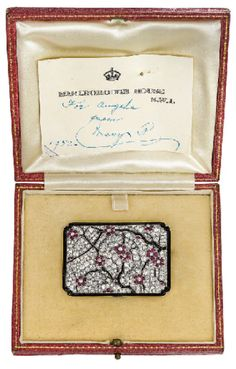 An exquisite diamond, ruby, and onyx brooch, by Lacloche Frères. Designed as a pavé-set diamond rectangular plaque with buff-top ruby flowers to the onyx branches and black enamel border, circa 1925, 5.2 x 3.6 cm, with French assay marks for platinum and gold, in fitted pink leather case Signed Lacloche Frères, No. 66252. Christie's.