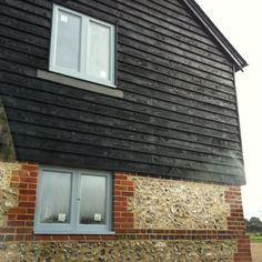 black barn board cladding with brick and flint and grey aluminium windows Black Cladding, Timber Cladding, Home Exterior Makeover, Exterior Remodel, Exterior Colors, Exterior Design, Outdoor Patio Shades, House Extension Plans, Extension Ideas
