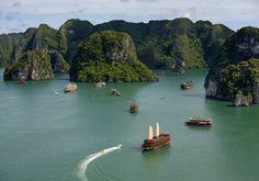 Statki, motorówki i inne wodne pojazdy pływające po wodach, pośród skał w Azji. Piękne klify, wybrzeża, urwiska porośnięte mchem i inną roślinnością. Spokojna, czysta woda, bez fal i jakiegokolwiek podmuchu wiatru.