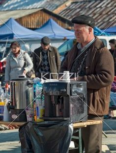 man with a coffee machine outdoor romanian market. - Image if a man with coffee machine standing in a market with people in the background.