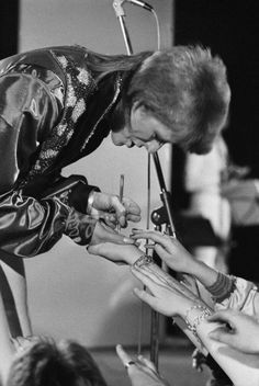 David Bowie signing a fan's hand, 1974. Photo by Terry O'Neill
