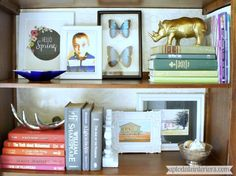 Tips for Styling a Bookcase - Up to Date Interiors  1: Start with your books.   some standing up/some  on side.  Put together small groups of books at a zig-zag pattern. The empty spots allow the space to breathe.Step 2:  Add in pictures and art work to fill about 1/3 of the space. Step 3:  Place smaller accessories on the stacked books and a few more to fill in some of the dead space Spread out colors & materials (lighter/darker accessories, silver, gold, brass)& heights.
