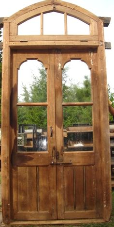 """Super cool solid Teak double exterior entry doors in jamb with arched glass transom window.   Comes complete with original hardware.  Ready to install.  Can be used interior as well.  Doors themselves measure 49"""" wide x 91 1/2"""" high."""