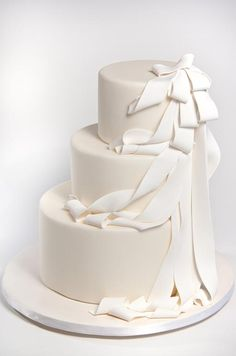 This off-center cream wedding cake is draped in flowing white fondant ribbons by sugar couture.
