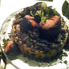 Small Chocolate Grooms cake with shaved chocolate and Strawberries on top.