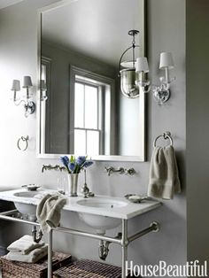 """""""I love this washstand from Waterworks, because I can hang wet towels without having to have towel bars everywhere,"""" Dixon says. Undermount basins and Etoile fixtures from Waterworks. Sconces by Crowder. Urban Smokebell lantern by Baker."""