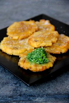 Tostones or patacones with aji criollo (Fried Mashed Plantains with Garlic). Typical dish from Costa Rica made with platains with fresly chopped tomato and guacamole. Banane Plantain, Panamanian Food, Venezuelan Food, Comida Latina, Plats Latinos, American Appetizers, Mashed Plantains, Costa Rican Food, Side Dishes