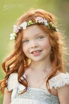Little ginger girl with pink Spring flowers in her hair