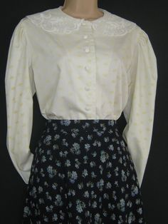 L A U R A A S H L E Y  I dont like ephemeral things, I like things that last forever  AN EXQUISITE, RARE EDWARDIAN STYLE BLOUSE IN 100% COTTON - POPULATED WITH DITSY FLORALS IN COWSLIP ON CREAM GROUND. CLASSIC, GENEROUS FIT WITH ELEGANT ROUND NECK WHICH IS ADORNED WITH A DELICATE, SCALLOPED LACE COLLAR IN WINTER WHITE. THE LEG-OF-MUTTON SLEEVES ARE MINUTELY GATHERED AT SHOULDERS AND TAPER INTO NOTCHED CUFFS WITH THREE FABRIC ROULEAU-LOOP BUTTON FASTENINGS. TWO REPLACEMENT BUTTONS ARE STILL…
