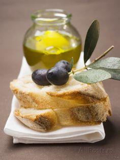 Olive Sprig with Black Olives on White Bread, Olive Oil Behind Lámina fotográfica