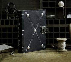This book is made of black leather, dyed and antiqued by hand. It was designed to resemble a medieval tome. The metal brads placed in the corners and the lock have a patina to fit the overall antique look of this book. The brads will allow it to lay flat when opened but the surface of the covers will never enter in contact with the table and thus will protect the decoration from scratching. I saw this system used in old books and I just loved it. The decoration is done by hot stamping with…