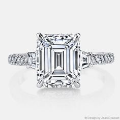 Lauren III by Jean Dousset, Starting at $14,400, with a 1 carat diamond center stone . More details: LAUREN III is a handcrafted three stones engagement ring with three rows of diamonds on the band - JeanDousset.com - pictured in Platinum set with a 3.00 Carats Emerald Cut diamond and 2 step-cut trapezoids.