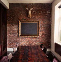 Coolest boardroom.  The mix of brick, ornate frame & blackboard & head.  Brilliant.