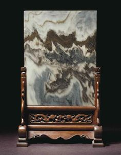 A dali marble and huanghuali table screen, Xiaozuopingfeng, 19th century. The attractive, variegated black and white stone panel is suggestive of a mountain range and is slotted into ahuanghuali stand with shoe feet and standing spandrels joined by an openwork panel carved with chilong and lingzhi. 17 in. (43.1 cm.) high Photo Christie's Image Ltd 2014