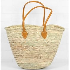 Bohemia Souk Shopper Basket In Mustard: Mustard Add a fun and casual lean to your weekend outfit with the Bohemia Souk Shopper Basket in Mustard. Perfect for popping to the shops on a sunny Saturday morning, the basket offers a roomy size for everything from essential groceries to a bunch of beautiful flowers. Ethically handmade in Morocco, it has been woven by artisans from sturdy and strong palm leaf, and is finished with mustard yellow rolled leather handles and contrasting stitch…