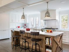 """Wondering how to keep an all-white kitchen from looking bland and boring? Simple: Just layer in plenty of natural texture. In this cottage-style space, for example, Jeremy Power of Bella Custom Homes used the center island to add warmth and interest. """"We built the island using reclaimed barn wood and topped it with a honed Carrara marble countertop,"""" he says. The """"X"""" details on each end are a subtle nod to the home's country roots."""