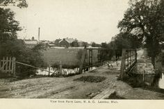 """his photograph shows animals walking down a bridge on Farm Lane with farm houses and fields in the background. The text on the front reads: """"View from Farm Lane, M.A.C. Lansing, Mich"""" Text on back: """"July 6th, '09."""