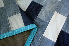 """4""""x8"""" denim bricks; running stitch with crochet cotton only on denim layer; quilt is tied so that ties do not show on front; backing us fleece; love the bright binding with running stitches also"""