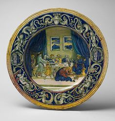 Dish with scene of Christ at Supper with Simon the Pharisee and with the Arms of Orsini Impaling della Rovere, 1528. Circle of Nicola da Urbino (Italian, active by 1520–died ?1537/38); lustered in the workshop of Maestro Giorgio Andreoli (Gubbio) Tin-glazed earthenware (maiolica), with luster.The Metropolitan Museum of Art. Felice della Rovere (d.1536), illegitimate daughter of Pope Julius II, married Roman nobleman Giangiordano Orsini (1506) and their arms appear together on this splendid…