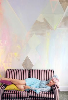 Diamond abstract pastel mural with metallic paint and neon yellow highlights, featuring vintage striped velvet couch with model lounging in pastel blue lace vintage dress and pink short hair.