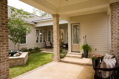 love the porch pillars and floor, edged in brick, stained trim, stairs are also brick, thresholds brick