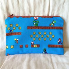 Mario Video Game Zipper Pouch Vividly colored fabric based on the Mario Bros video games. Light blue matching lining. Brick red zipper. 7 inches long. Brand new, never used. Great to keep makeup, pencils, coupons, and other collectibles organized! 100 percent cotton. ELLY TNT accessories Bags Mini Bags
