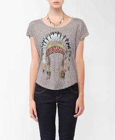 A heathered top featuring a colored headdress graphic and a round neckline. Short raw edge sleeves. High-low hemline. Oversized fit. Knit. Lightweight.