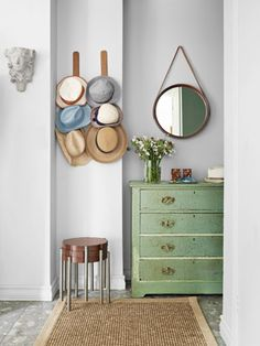 Use notched leather straps to create a wall display for hats, bags, and scarves. #decorating