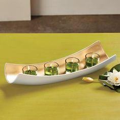 """Embrace Centerpiece A modern curve lined with a gold finish is illuminated by the glow of four votives or tealights, sold separately. Matte-finished white resin centerpiece includes four glass votive cups. 3½""""h, 16½""""l."""