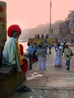 This magical scene is timeless, it was shot in the afternoon of Xmas day in Varanasi (Benaras).  On the left a well known sadhu form the ghats, I saw in a book that his dreadlocks are two meters long.  Three men are wearing typical clothes from South India, one is taking in picture his friend who has a big snake around his neck.  The owner of that snake wears an orange turban on the right.    Walking along the ghats of river Ganga is one of the most magical thing in the world.