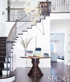Home with white walls, dark wood floors, round wooden coffee table, staircase with wood steps and dark carpet, and large brass light fixture