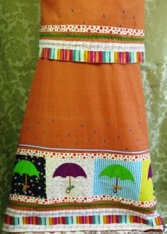 Burnt Sienna colored linen rida designed using a 'Monsoon' theme. Rainbow colored laces, trims and patches are used along with felt umbrellas, touch of hand painted water drops and hand embroidery. A must have !!