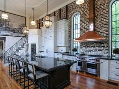This beautiful large kitchen from designer Bryan Reiss takes advantage of the present architecture with an exposed brick wall and arched leaded glass windows. The kitchen accents this beautiful wall by including a large copper range hood over its professional stainless steel range.