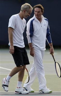 Former tennis greats John McEnroe and Jimmy Connors walk off the court after hitting tennis balls at the U.S. Open in New York,  September 2009