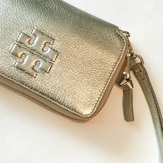 """Tory Burch Metallic Gold Thea Wristlet This AUTHENTIC Tory Burch leather Thea Wristlet in a muted metallic textured gold leather. Unobtrusive in coloring, very stunning! ❤️ This is perfect for everyday use or special occasions. Excellent pre-loved condition. For those of us who enjoy carrying minimal with them this wristlet is great. Gold hardware. Zip around closure. 6"""" W X 4.5"""" H  X approx. 1"""" D. Holds your phone and up to six credit cards/I.D...even some lip glosses/sticks 💄👛💄👛. This…"""