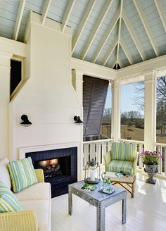 Charleston screened porch - blue ceiling // shutters // glossy white floor // fireplace // sconces