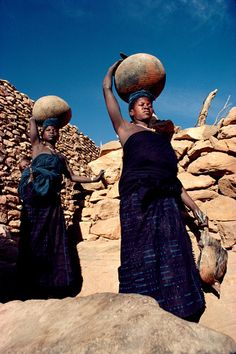 Dogon women fetching water in earthenware jars. Each jar holds about 25 litres. The women wear indigo dyed clothing. Mali.  | © Bryan & Cherry Alexander Photography