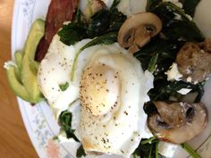 Poached eggs over sautéed kale, spinach, mushrooms and turkey sausage. Side of turkey bacon and avocado slices.