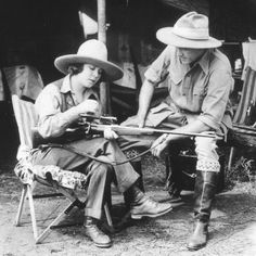 A vintage picture illustrates Safari fashion in the early 20th century. The woman is holding a gun while being dressed in complete Safari attire. This image shows that women are now finally starting to be included in a male dominated world due to the rise of this fashion.