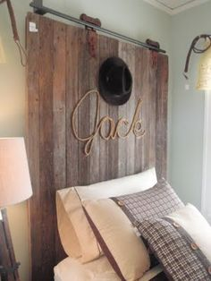Cute headboard for a little cowboy, made from old barn door. Name written with rope. Too Cute!