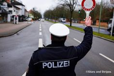 Americans in Germany without a current stateside driver's license scrambling to avoid penalties for driving illegally are encountering conflicting information from local authorities. German police officer David Giesler motions to a motorist on Mannheimerstrasse, in Kaiserslautern, Germany, while conducting a random traffic check on Jan. 28, 2014. (Joshua DeMotts/Stars and Stripes)