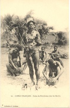 Translated caption reads: ''French Congo. Scene of Fetichism in the Bavilis country''. In the foreground statuettes on the ground, sorcerer holding statuette in his left hand and a stick in his right hand, ornaments around his neck. Behind him two musicians and children in the background.Congo Français. Photograph by J. Audema. ca. 1905