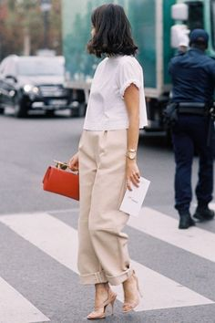 Great stylish business outfit, beige trousers, white top and red bag