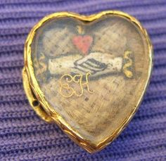 """When was the last time you saw something authentic which was dated 1687? I love hearts, and hands. There is a bed of white hair, and on top of that are clasped hands, with a heart above the hands. Below the hands is the scribe """"EH."""" This could either be sentimental or mourning. I have seen hands and hearts on mourning pieces, symbolizing that the two were together in death, but this could also be a love token."""