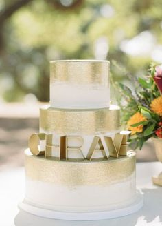 Featured Photographer: Sylvie Gil, Featured Cake: Sweet on Cake; Elegant gold and white wedding cake with shimmering detail