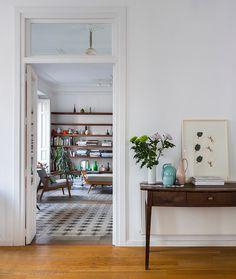 Sobre una mesa de madera tocinera, jarrón blanco de Sargadelos, grabado de Peter Neuchs de edición Benveniste. El resto de piezas de cerámica son de Helena Rohner, y en concreto, el rosa, un prototipo diseñado para Kahler.