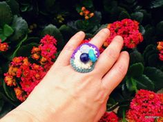 Crochet ring with glass- plastic beads, on tin ring base.