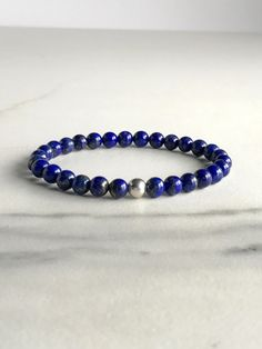 This natural crystal bracelet features genuine Lapis Lazuli gemstones. The vibrant cobalt blue stones have some subtle natural gold flecks. Choose either a gold or silver accent bead in the dropdown menu at checkout. Or chose both bracelets, and save $5! MATERIALS & DIMENSIONS • Wrist Measurement: Upon ordering, your bracelet will be made to fit you. All you need to do is measure your wrist before ordering to ensure a good fit. Ordering as a gift? The average wrist measurement for women i...