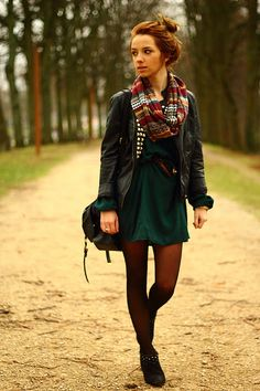 Dark green dress, leather waist belt, black leather jacket, black ankle boots, black opaque tights, printed infinity scarf, bun hairstyle.