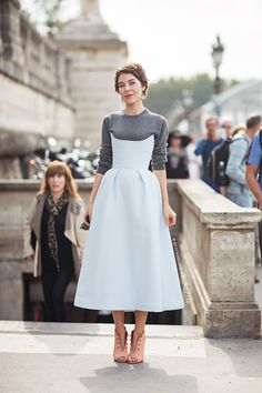 Ulyana Sergeenko in a powder blue strapless bustier dress over a gray sweater, and pink booties.